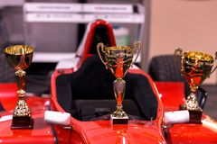 Trophies for winner and red racing car. Closeup Royalty Free Stock Photos