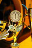 Trophies for winner and yellow wheel of racing car. Background stock photo