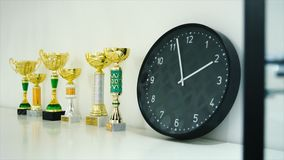 Trophy award for the winner show on shelf. Stock. Clock and trophies on the shelf. The concept of time and sports.  stock photo