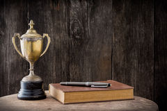 Trophy, book and pen Royalty Free Stock Photo