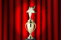 Trophy cup. Golden trophy cup on red curtain background royalty free stock photography