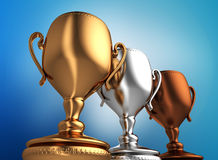Trophy cups. 3d illustration of three trophy cups over blue background Royalty Free Stock Photography