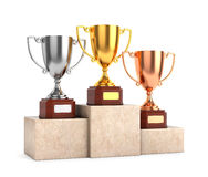 Trophy cups on pedestal. Three award goblet trophies: gold, silver and bronze trophy cups on marble pedestal isolated on white background stock images