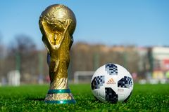 Trophy of the FIFA World Cup. April 9, 2018 Moscow, Russia Trophy of the FIFA World Cup and official ball of FIFA World Cup 2018 Adidas Telstar 18 on the green Stock Images