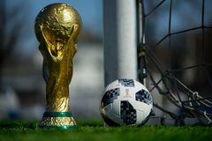 Trophy of the FIFA World Cup. April 9, 2018 Moscow, Russia Trophy of the FIFA World Cup and official ball of FIFA World Cup 2018 Adidas Telstar 18 on the green Stock Photos