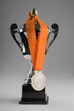 Trophy with silver medal. Trophy on grey background with silver medal on a orange ribbon Royalty Free Stock Photos