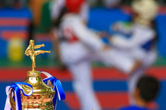 Trophy for Taekwondo contest with athletes fighting in backgroun Royalty Free Stock Photography