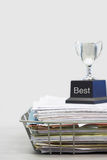 Trophy on Top of Papers saying best.  Stock Images
