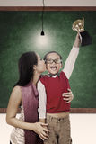 Trophy and winner kiss by mum at class. A mother is kissing her son for winning a trophy at school Stock Photography