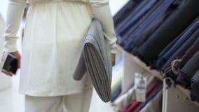 Tropić materiał filmowego piękna kobieta w bielu, chodzi sukiennym sklepem z rolką lekka tkanina w dobrze zdjęcie wideo