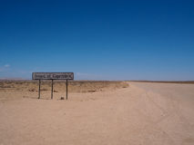 Tropic of capricorn line signage along the desert road with blue. Tropic of capricorn line signage along the desert road in Namibia with blue sky Stock Photography