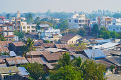 The tropic forests behind Mandalay skyline, Myanmar. The foggy tropic forests are seen behind the roofs of Chanayethazan township in Mandalay, Myanmar stock photography