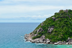 Tropic island. Green tropical island with a rocky shore Stock Images