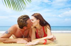 Tropic kiss. A portrait of attractive couple having kiss on the beach Stock Photography