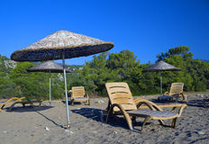 Tropic parasols on shingle beach. Yellow tropic parasols and beach chairs on shingle beach in sunny weather Stock Images