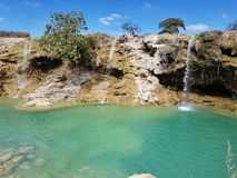 Tropic waterfalls with blue water royalty free stock photos