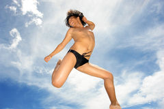 Tropical acrobat on beach. Sky-high acrobatic jump by Asian male dancer in the tropics. Concept of success, soaring, enthusiasm, sports, active lifestyle royalty free stock photos