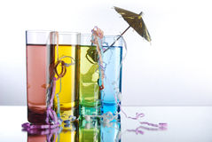 Tropical alcohol. Four mult-colored shot glasses with colored alcohol on a reflective surface with party popper string and umbrella stock images