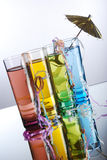 Tropical alcohol. Four mult-colored shot glasses with colored alcohol on a reflective surface with party popper string and umbrella stock photography
