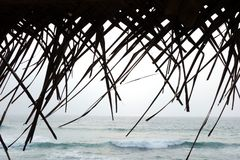 Tropical Backdrop of Ocean with Thatched Roof stock photos