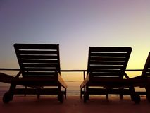 Tropical background with couple of deck chairs at sunset by sea. It is beautiful view of golden sun royalty free stock photo