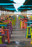 Tropical Bar and Grill. Colorful bar tables, stools and umbrellas at a beachside bar and restaurant Royalty Free Stock Image