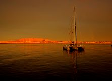 At a Tropical Bay. A trimaran sits quietly as anchor in a tropical bay in Baja Mexico stock image