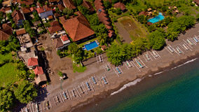 The tropical bay with stony beach. The tropical bay with stony beach, boats and buildings, aerial view. Village of Amed, Bali, Indonesia stock images