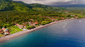 The tropical bay with stony beach. The tropical bay with stony beach, boats and buildings, aerial view. Village of Amed, Bali, Indonesia Royalty Free Stock Photos