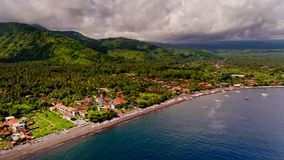 The tropical bay with stony beach. The tropical bay with stony beach, boats and buildings, aerial view. Village of Amed, Bali, Indonesia stock photography