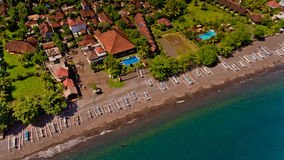The tropical bay with stony beach. The tropical bay with stony beach, boats and buildings, aerial view. Village of Amed, Bali, Indonesia Royalty Free Stock Images