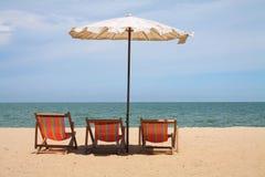 Tropical beach. Deckchairs and parasol on the white sand beach facing cha-am beach, Thailand Royalty Free Stock Photo