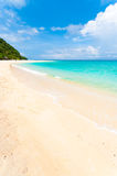 Tropical beach. Tropical white beach with a few tourists at the end Royalty Free Stock Photo