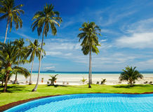 Tropical beach. With coconut palms and swimming pool Stock Photos