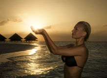 Tropical beach. Beautiful girl holding the sun in her hands Stock Photography