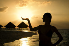 Tropical beach. Beautiful girl holding the sun in her hands Royalty Free Stock Photos