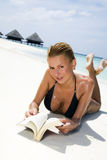 Tropical beach. Girl reading a book on the seashore Royalty Free Stock Photography