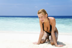 Tropical beach. Woman playing with the sand. Copy space Stock Images