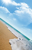 Tropical beach. Sea waves on tropical beach and clouds with sun rays in the background royalty free stock image