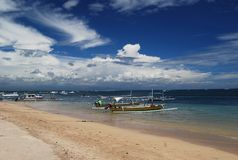 Tropical beach. With boats along the shore of the ocean, Bali, Indonesia Stock Image