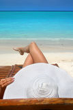 Tropical beach. Woman with big white hat relaxing on the beach Royalty Free Stock Photography