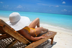 Tropical beach. Woman with big white hat relaxing on the beach Stock Image