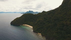 Tropical beach, aerial view. Tropical island. Wild beautiful beach with coconut palms. Tropical bay in El Nido. Aerial view: bay and the tropical island. Aerial stock footage