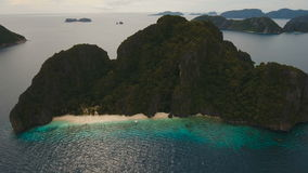 Tropical beach, aerial view. Tropical island. Wild beautiful beach with coconut palms. Tropical bay in El Nido. Aerial view: bay and the tropical island. Aerial stock video footage