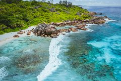 Tropical beach Anse Cocos. La Digue island. Seychelles. Drone aerial view of coastline with blue ocean waves, unique stock photos