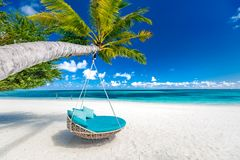 Tropical beach background as summer landscape with beach swing or hammock and white sand and calm sea for beach banner