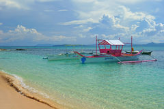 Tropical beach. Beautiful tropical beach with a pink boat waiting for tourists.Siargao Island, Philippines stock photos