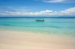 Tropical beach with boat on mooring buoy Royalty Free Stock Photography