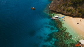 Tropical beach with boats, aerial view. Tropical island. Beautiful beach with boats and tourists. Tropical bay in El Nido. Aerial view: bay and the tropical stock video footage