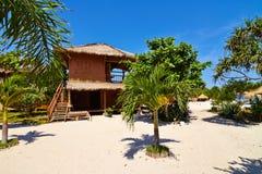 Tropical beach bungalow on ocean shore Stock Image
